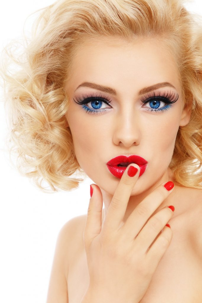Young beautiful sexy blonde with stylish make-up and hairdo and touching her lips, on white background